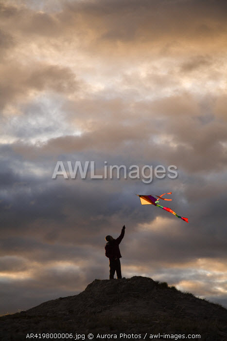 awl-images.com - Canada / Silhouette of a woman flying a colorful kite atop a hill