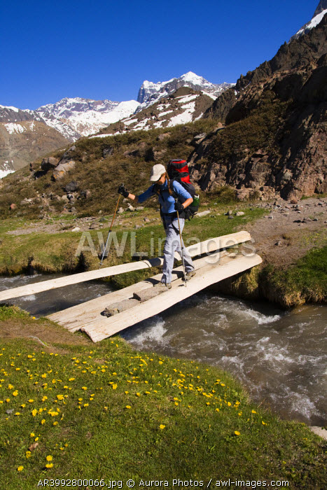 awl-images.com - Chile / A woman crossing a stream on a log bridge near Volcan San Jose in Chile
