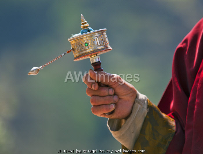 A Buddhist spins his hand-held prayer wheel in a clockwise direction with the help of a weighted chain attached to it.  Each turn is the equivalent of reading the prayers or mantras within.