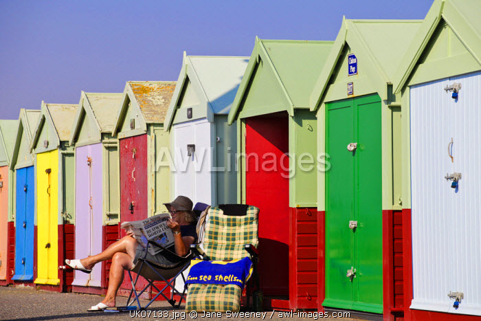awl-images.com - UK, England / UK, England, Sussex, Hove, Woman reading newspaper infront of Beach huts (MR)