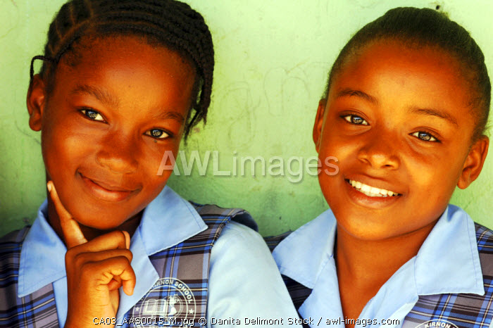 Antigua, St John, close-up portrait of an African schoolgirl with hand on chin by a friend smiling (MR)