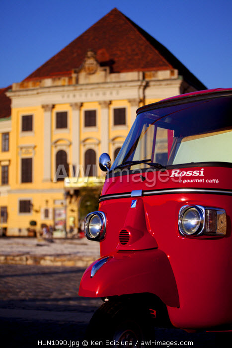Hungary, Budapest, Central & Eastern Europe, A red mini-van with castle buildings in the background