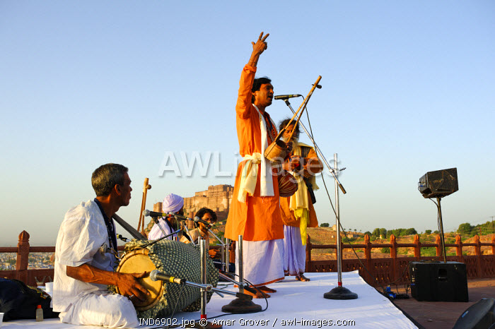 India, Rajasthan, Jodhpur. Framed by the massive Mehrangarh Fort, Baul musicians at the Rajasthan International Folk Festival,  perform at one of the dawn recitals.