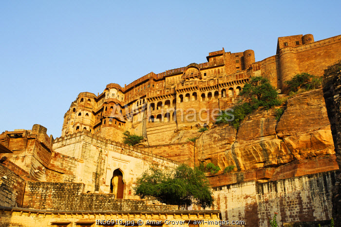 India, Rajasthan, Jodhpur. Perched atop a sheer rocky bluff, the main palace buildings of Mehrangarh Fort are guarded by a muscular arrangement of fortifying walls and gateways.