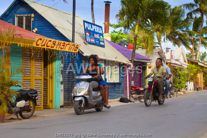 Dominican Republic, Samana Peninsula, Las Terrenas, People riding motorbikes past former Fishermans huts which are now trendy restaurants