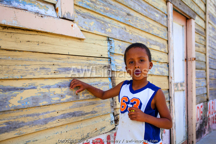 Dominican Republic, Rio San Juan, Boy standing by old wooden house