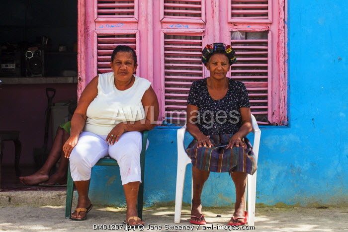 Dominican Republic, Rio San Juan, Two women sitting outside house with pink shutter windows