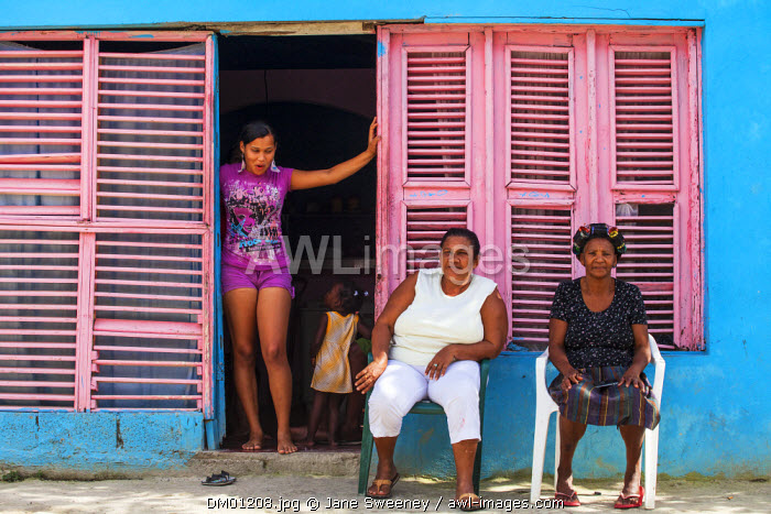 Dominican Republic, Rio San Juan, Family outside house with pink shutter windows