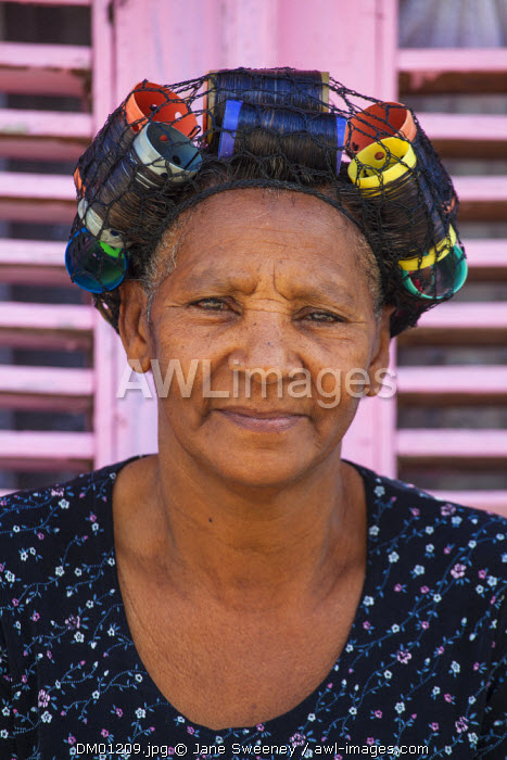 Dominican Republic, Rio San Juan, Woman sitting outside house with pink shutter windows