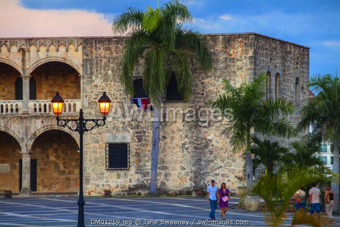 Dominican Republic, Santa Domingo, Colonial zone, Couple holding hands walking past Plaza Espana, Alcazar de Colon