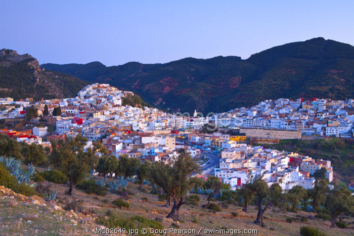 Elevated view over the historic hilltop town of Moulay Idriss illuminated at sunset, Morocco