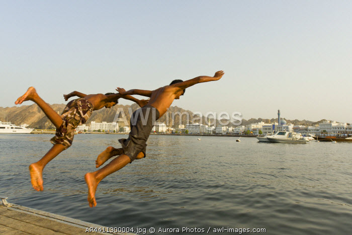 awl-images.com - Oman / Muscat, Oman: Two Boys Dive From A Pier Into The Water Of Sultan Qaboos Port In Muscat, Oman.