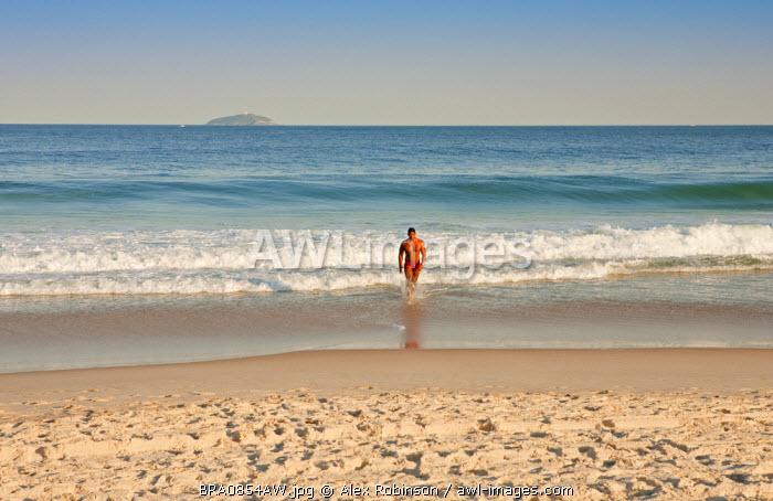 South America, Rio de Janeiro, Rio de Janeiro city, a man in a red sunga (speedos) on Copacabana Beach