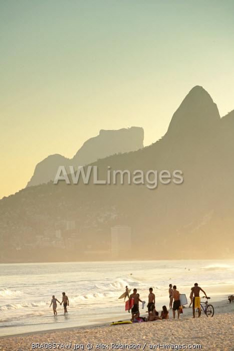 South America, Rio de Janeiro, Rio de Janeiro city, Ipanema, sunbathers on Ipanema beach with the Dois Irmaos mountains in the background