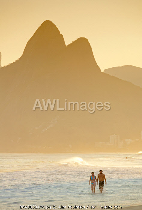 South America, Rio de Janeiro, Rio de Janeiro city, Ipanema, a couple walking through the surf holding hands on Ipanema beach with the Dois Irmaos mountains in the background