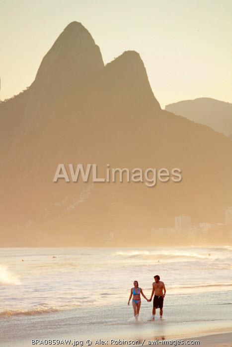 South America, Rio de Janeiro, Rio de Janeiro city, Ipanema, a couple walking through the surf holding hands on Ipanema beach with the Dois Irmaos mountains in the background