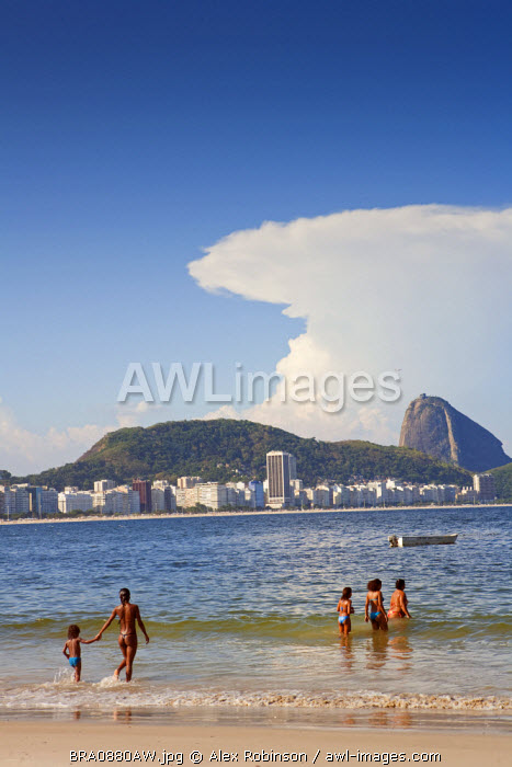 South America, Rio de Janeiro, Rio de Janeiro city, swimmers at the end of Copacabana Beach with Copacabana and the Morro do Leme hill in the background