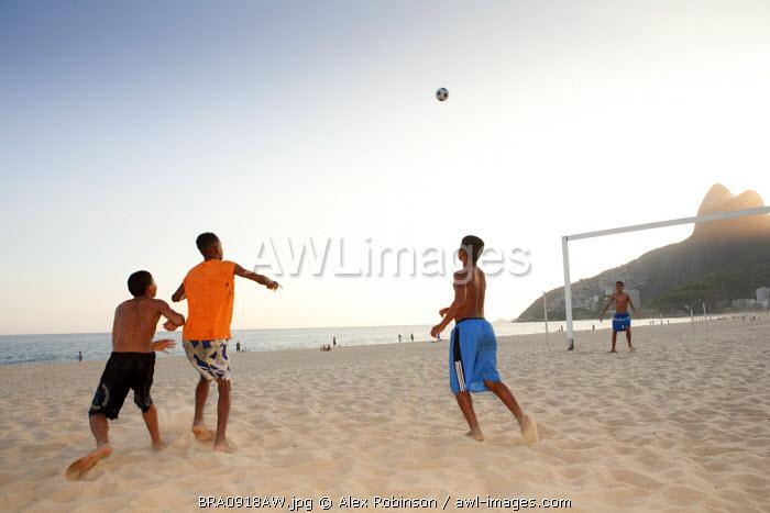 South America, Rio de Janeiro, Rio de Janeiro city, Ipanema, boys playing football on Ipanema beach in front of the Dois Irmaos mountains