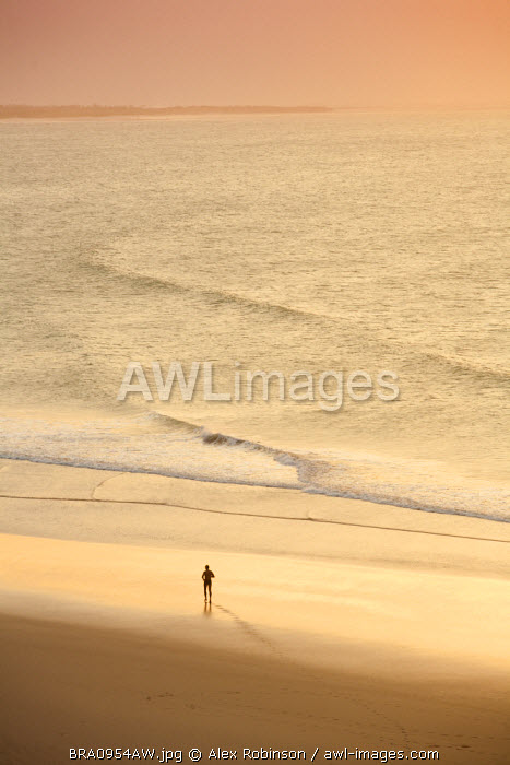South America, Brazil, Ceara, Jericoacoara, A man jogging along the beach at sunset seen from the Sunset dune