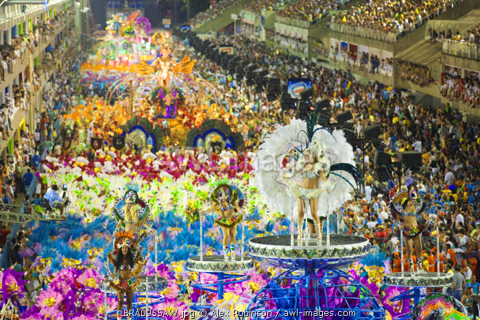 South America, Rio de Janeiro, Rio de Janeiro city, costumed dancer in a feather headdress and the floats and dancers of the Caprichosos samba school at carnival in the Sambadrome Marques de Sapucai