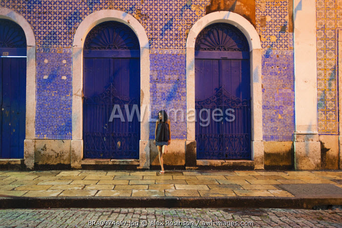 South America, Brazil, Maranhao, Sao Luis, a girl stops for a rest in a colonial street in the city centre, a UNESCO World heritage site
