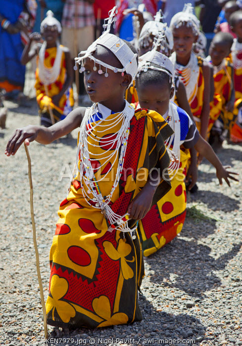 Young Maasai schoolgirls practise for an inter-schools song and dance competition at Magadi. The circular marking on her cheek as well as her white beaded ornaments denote that she is a Kisongo Maasai, Kenya