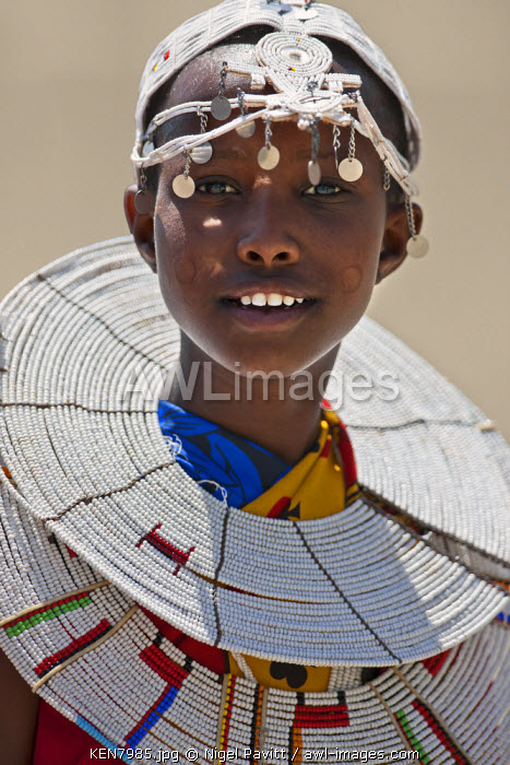 A young Maasai girl at Magadi. The circular markings on her cheeks as well as her white beaded ornaments denote that she is a Kisongo Maasai, Kenya