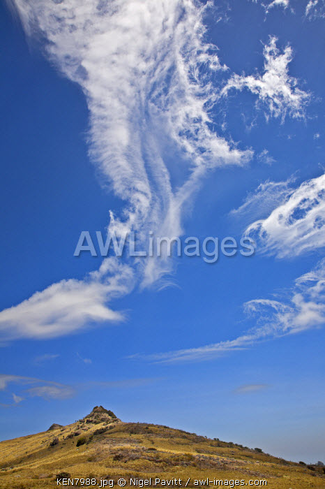 In strong wind, white clouds spiral over a moorland peak of the Aberdare Mountains, Kenya