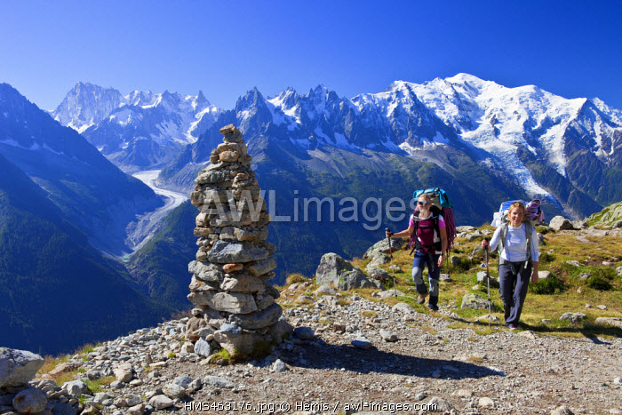 France, Haute Savoie, Chamonix Mont Blanc, cairn in Reserve naturelle nationale des Aiguilles Rouges (Aiguilles Rouges National Nature Reserve) with a view of Mont Blanc (4810m) on the right and of Mer de Glace, climbers on the march for the Aiguille de La Perseverance