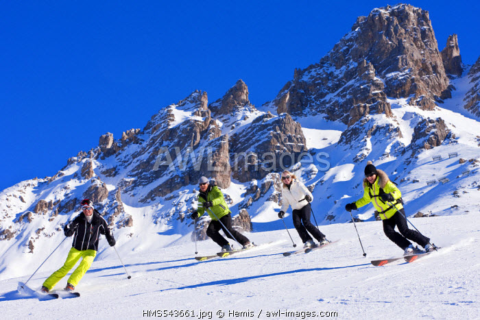 France, Savoie, Meribel, massif of Vanoise, Tarentaise Valley, ski slopes of 3 valleys, couples skiing with a view of the Croix de Verdon or Dent de Burgin (2739m)
