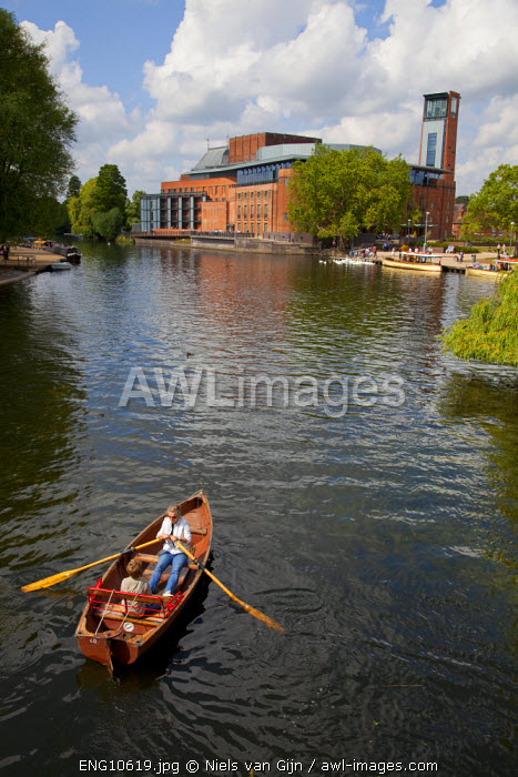 UK, Stratford upon Avon. Tourists row along the River Avon towards the Royal Shakespeare Company Theatre.