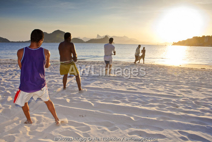 awl-images.com - Brazil / South America, Brazil, Rio de Janeiro state, Niteroi, fishermen pulling in the net on Charitas beach at sunset with Corcovado in the distance