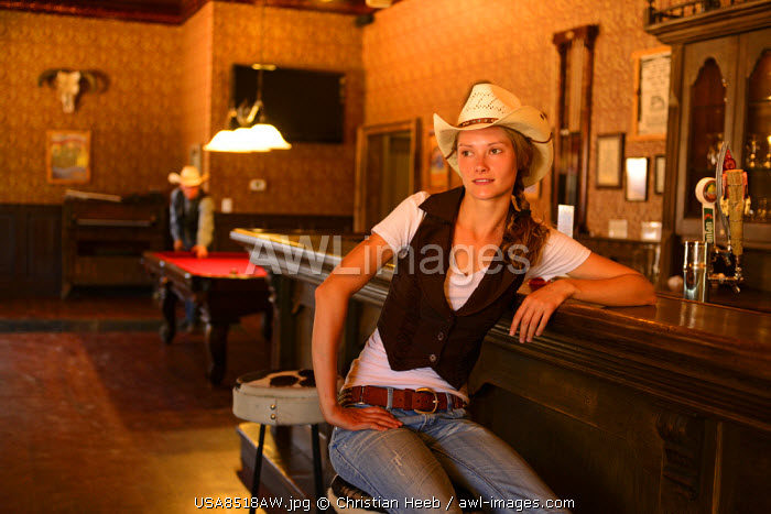 awl-images.com - USA / Cowgirl sitting at bar in Old Saloon at Apache Spirit Ranch, Tombstone, Arizona, USA MR