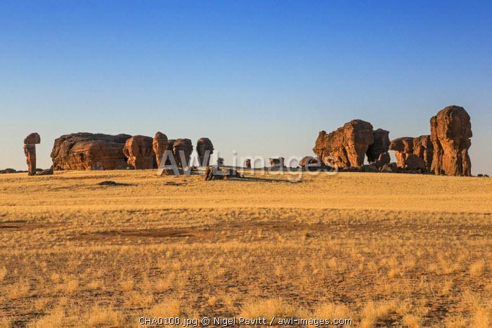 Chad, Abaike, Ennedi, Sahara. Weathered red sandstone columns in a desert landscape.