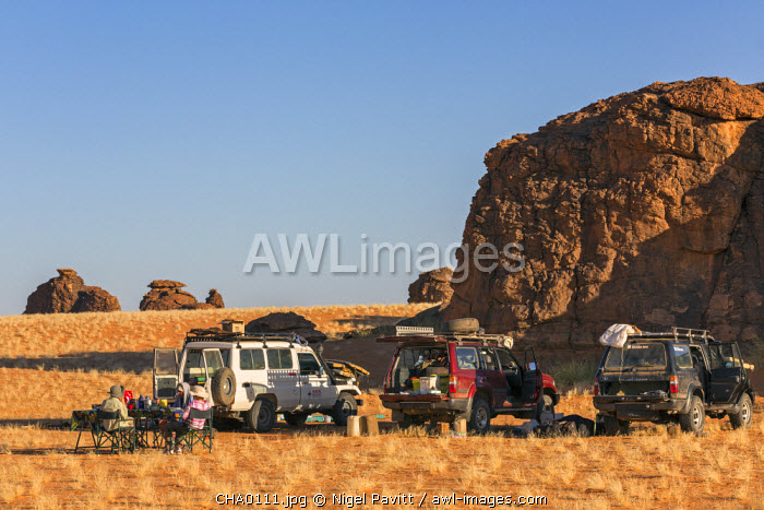 Chad, Abaike, Ennedi, Sahara. Visitors to Abaike having breakfast after packing up camp.