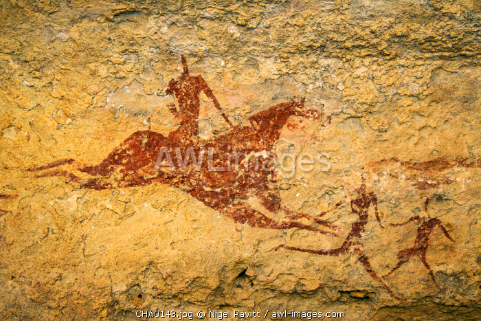 Chad, Terkei East, Ennedi, Sahara. A painting on sandstone of a galloping horse and rider behind two running figures.