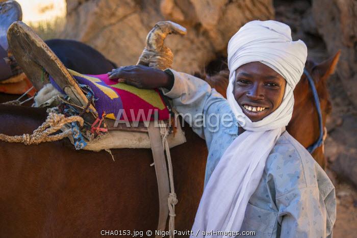 Chad, Barakatra, Ennedi, Sahara. A happy young Tubu boy beside the saddle of his horse.