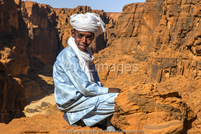 Chad, Wadi Archei, Ennedi, Sahara. A young Toubou boy on a ledge overlooking Wadi Archei.