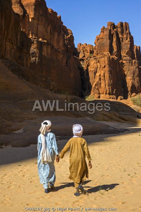 Chad, Wadi Archei, Ennedi, Sahara. Two young Toubou boys walk along Wadi Archei.