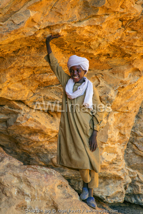 Chad, Wadi Archei, Ennedi, Sahara.  A Toubou boy at the entrance to a large sandstone cave.
