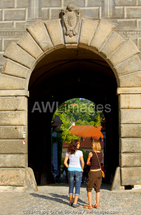 Central and Eastern Europe, Czech Republic, South Bohemia, Cesky Krumlov. Two young woman on front of the entrance to the Castle. MR