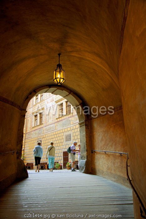 Central and Eastern Europe, Czech Republic, South Bohemia, Cesky Krumlov. People walking through a tunnel leading to the castle courtyards.