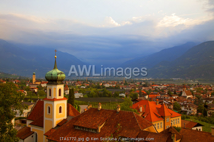 Northern Italy, Trentino, Alto Adige, Sud Tyrol. Overview of the town of Lana with a church in the foreground and mountains in the background