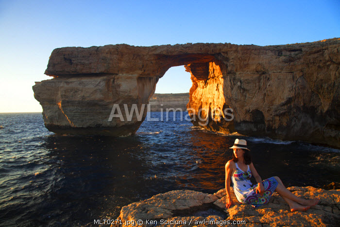 Mediterranean Europe, Maltese Islands, Gozo. Young woman enjoying the scenery of the Azure Window in Dwejra. MR