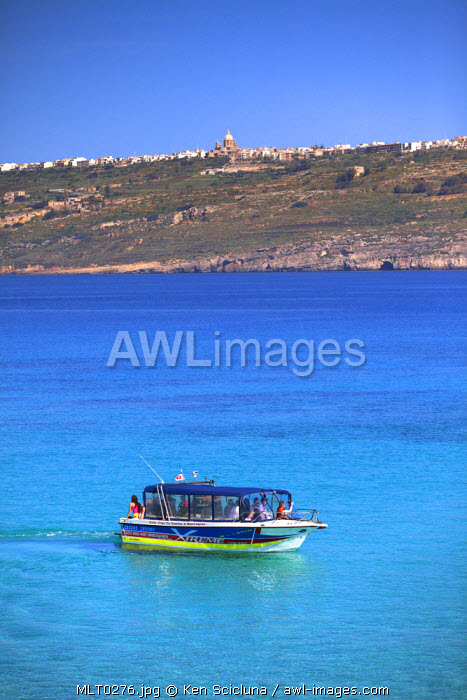 Mediterranean Europe, Maltese Islands, Comino. A boat in the clear blue waters of the Blue Lagoon with Gozo visible in the background.
