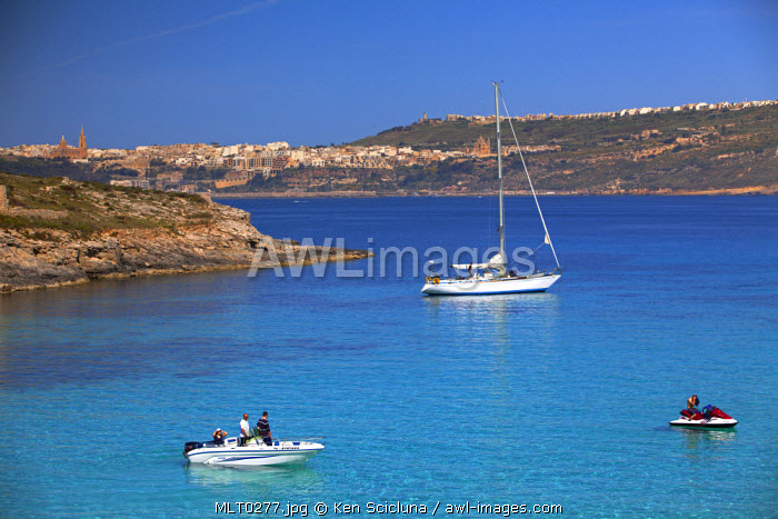 Mediterranean Europe, Maltese Islands, Comino. A yacht, jet ski and speed boat in the Blue Lagoon with Gozo visible in the background