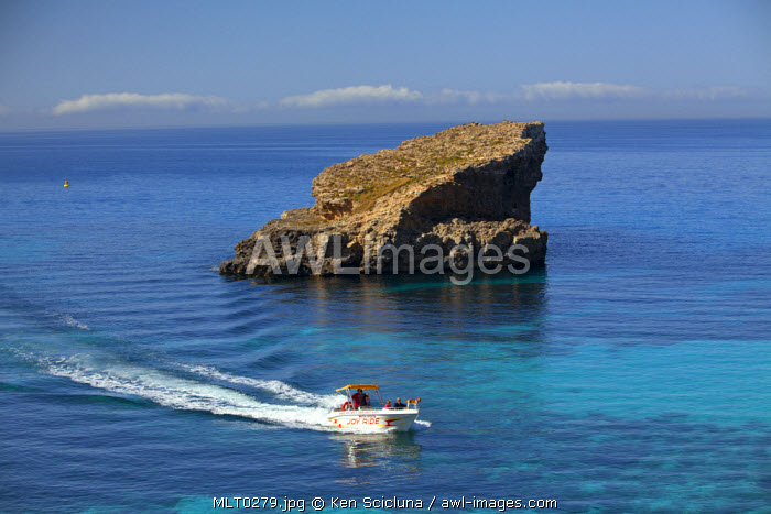 Mediterranean Europe, Maltese Islands, Comino. A boat moving in the clear blue waters of the Blue Lagoon