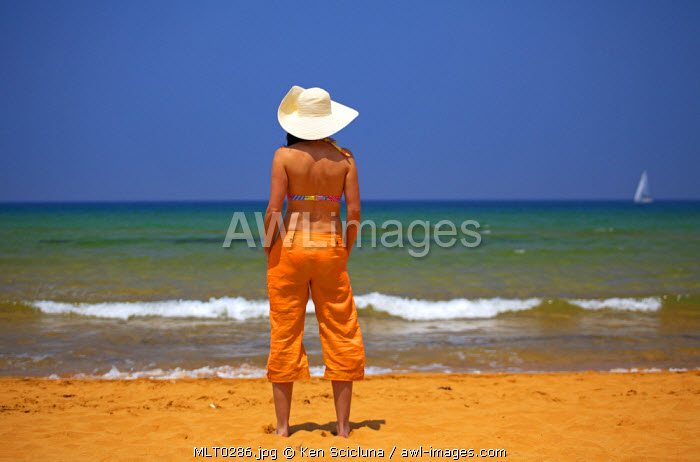 Mediterranean Europe, Maltese Islands, Gozo. A young woman enjoying the sun and sea on the beach in Ramla Bay. MR