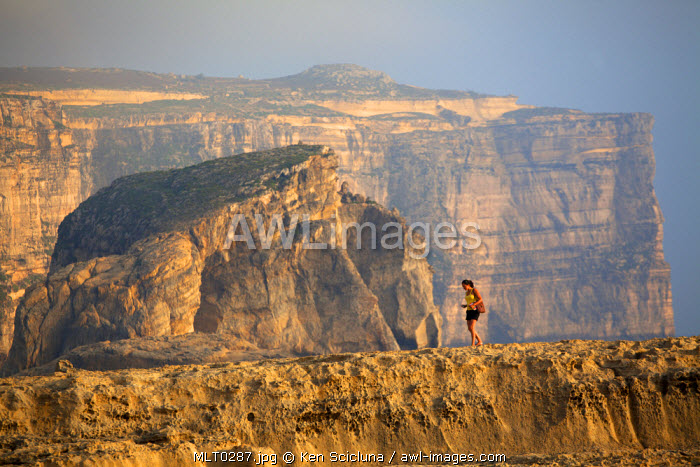 Mediterranean Europe, Maltese Islands, Gozo. Young woman walking amidst gigantic stones and cliffs in Dwejra