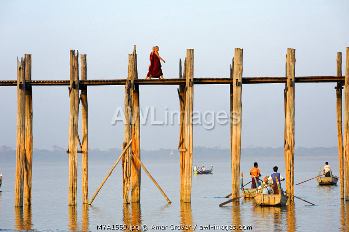 Myanmar, Burma, Mandalay Region, Mandalay. Monks stroll across the celebrated teak-built U Bein's Bridge which crosses  Taungthaman Lake near Mandalay.